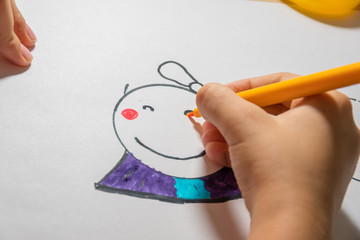 Girl draws a picture of a girl with a felt-tip pen