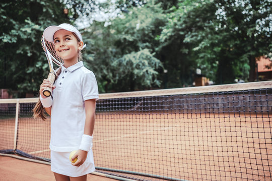 Child playing tennis on outdoor court. Little girl with tennis racket and ball in sport club.