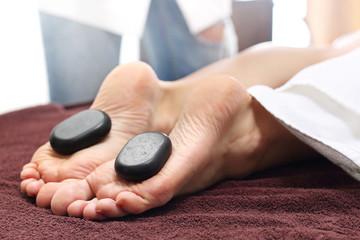 Relaksacyjny masaż kamieniami. Kobiece stopy z kamieniami bazaltowymi, relaks w salonie spa.