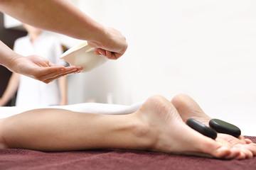Masaż kamieniami. Kobiece stopy z kamieniami bazaltowymi, relaks w salonie spa.
