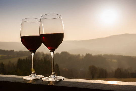 Two wine glasses at sunset time.