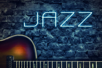 Vintage guitar and a neon inscription Jazz on the background of an old brick wall. Concept music.