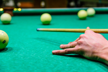 Player arm with the cue and balls on the green cloth. Russian billiard
