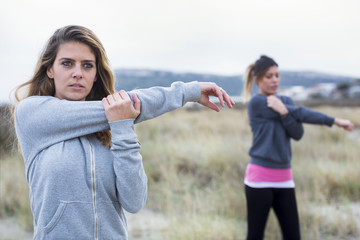 Due amiche in tuta da ginnastica si allenano in mezzo a una spiaggia