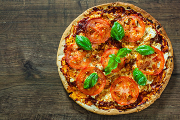 Pizza with Mozzarella cheese, Tomatoes, pepper, Spices and Fresh Basil. Italian pizza. Pizza Margherita or Margarita. on wooden background. with copy space. top view