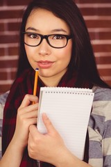 Attractive hipster posing with a pencil and a book