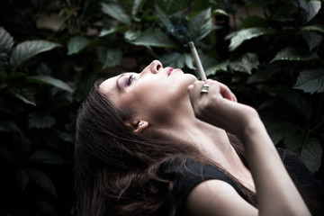 portrait of young woman with cigarette in garden profile