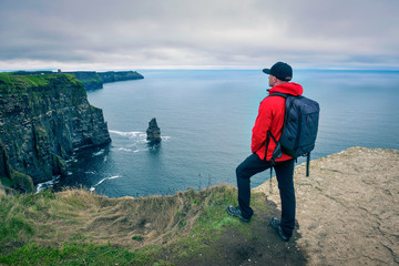 Wall Mural - Young hiker standing at the cliffs of Moher