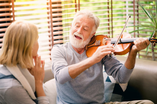 Meaningful moments. Lover senior couple sing a song together. Hasband playing his violin for his beloved wife.
