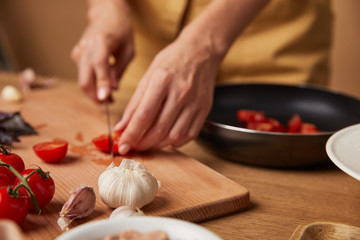 close-up shot of woman cutting cherry tomatoes for pasta