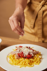 cropped shot of woman putting grated cheese onto pasta in plate
