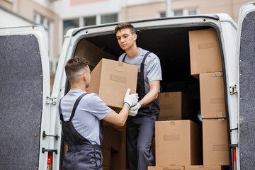 Two young handsome movers wearing uniforms are unloading the van Wall mural