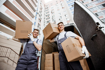 Two young handsome smiling workers wearing uniforms are standing