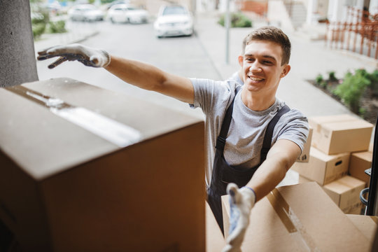 A young handsome smiling mover wearing uniform is reaching for the box while unloading the van full of boxes. House move, mover service.