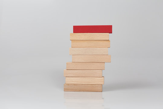 Red block top of wooden tower on white background