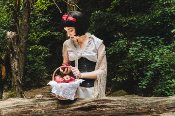 Snow White is in the forest, holding and looking to a red apple next to a basket full of apples. Fotomurales