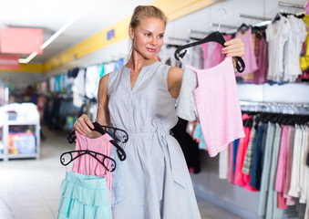 Person is choosing clothes for daughter