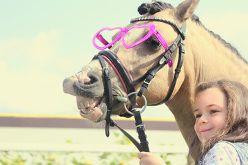 happy girl with pony horse with smile and heats glasses