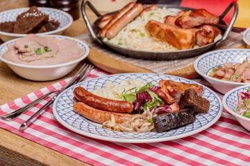 Oktoberfest food menu: sausages, fried bacon, pork ears, salad.