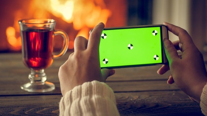 Toned closeup image of female hands making photo on smartphone of tea and burning fireplace at night. Empty green screen for inserting your own picture or text