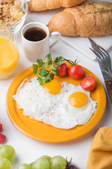 Breakfast with tomato fried egg and cheese, almond, grape, berry, coffee,orange juice on white isolated background