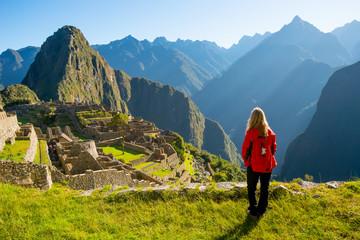 Woman looking at Machu Picchu at sunrise