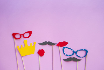 Colorful photo booth props glasses, lips, crown and moustaches on pink background with copyspace.
