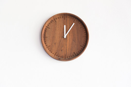 round wooden clock on white concrete wall, show time on mid day for launch time.