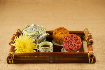Tray with tasty tea and round moon cakes for mid autumn festival