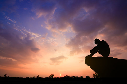 Silhouetted photo. Lonely man sitting on cliff. He is unhappy and sad. He is watching the evening glow. Photo concept for Silhouetted and depression.
