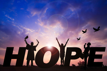 Hope word Silhouette sunset background.They are standing  between hope word. expectation ,objective, Photo Silhouette and hope  concept idea. Wall mural