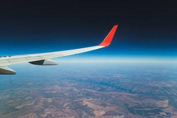 Side/top view of a airplane wing and the earth with a deep blue sky, a cold horizon and a green ground. Travel, Airplane, Vocation, transport, fly is the concept