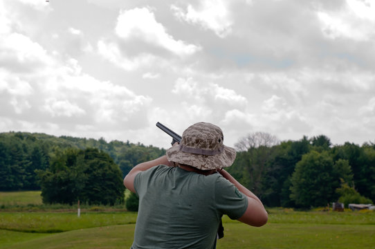 A man trap shooting with a 12 gauge shotgun on a beautiful summer day with big white clouds in the sky and a forest treeline in the background in Pennsylvania, USA