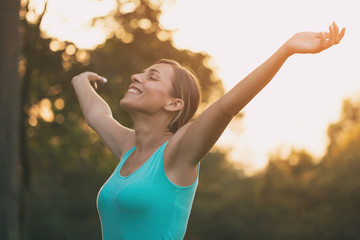 Beautiful woman enjoys with her arms outstretched in the nature.