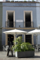 Bar La Concepcion with some tables, white awning and a palm tree in Santa Cruz de Tenerife, Spain