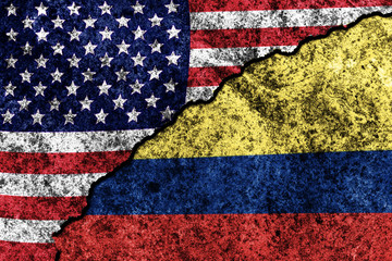 two flags of the USA and Colombia on a cracked concrete wall