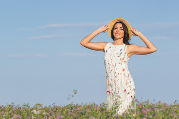 Beautiful young woman on the field of clover
