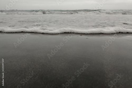 A close view of the sea undertow in the Almaciga black sand beach