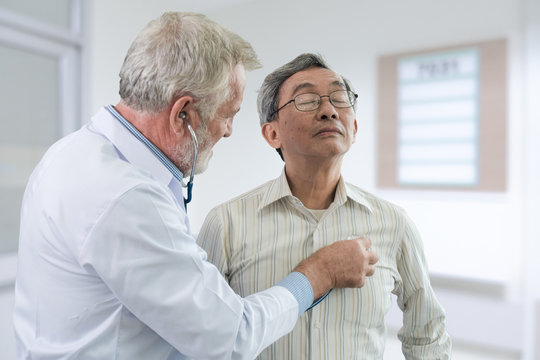 The senior doctor listen the heart of the elderly patient