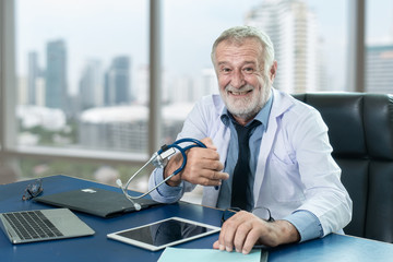 Senior doctor sitting on chair with feel cheerful