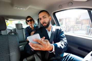 Fototapete - Taxi driver showing a mobile phone to female passanger