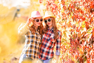 Wall Mural - Two Young Girl Enjoy Nature in Autumn Park. Best friends Walking Relax on Colorful Fall leaves background, Outdoor. Beautiful Woman in Stylish Outfit, Trendy Sunglasses