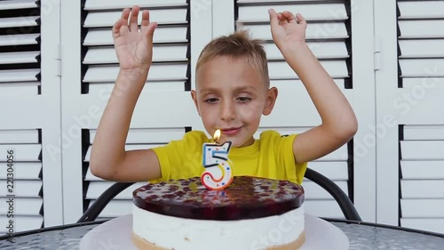 Lovely Fifth Year Old Boy In T Shirt Celebrating His Birthday Blowing Candles On Homemade Baked Cheesecake Indoor White Background