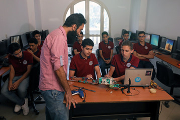 Students present to a teacher in a classroom a prototype navigational smart stick designed to help visually impaired people in Cairo