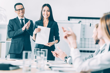 rewarded happy asian manageress holding blank paper while colleagues clapping to her