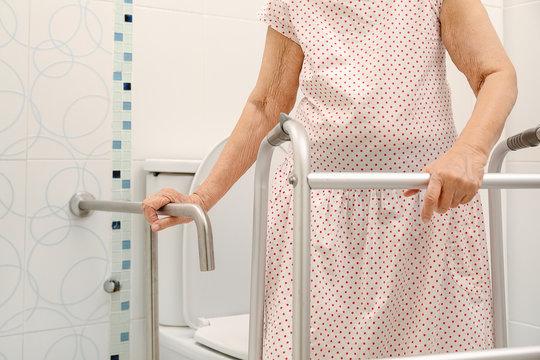 Elderly woman holding on handrail in toilet.