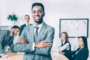 handsome african american manager with crossed arms with blurred multicultural colleagues on background