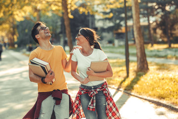 Young student couple going to college class.They walks trough university campus and laughing.Autumn.