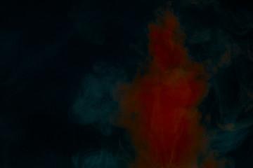 red paint dissolves under water on a dark background