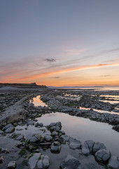 Sunset at Kilve Beach, Somerset, with Limestone (Blue Lias) wave cut platform, with rock pools  and reflections